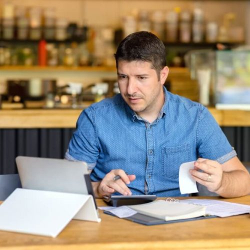 Mature restaurant owner calculating finance and bills of new business  – Entrepreneur online using tablet and calculator to work and calculate financial expenses of small coffee shop business start-up; Shutterstock ID 1451408156; Job: NL Q3 Comercial; Client/Licensee: Banco Popular; Other: Comercial