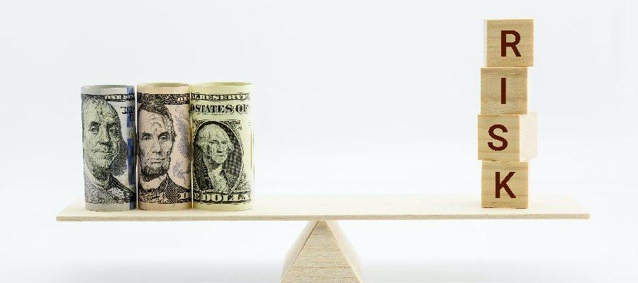 Dolares en una balanza con la palabra riesgo
