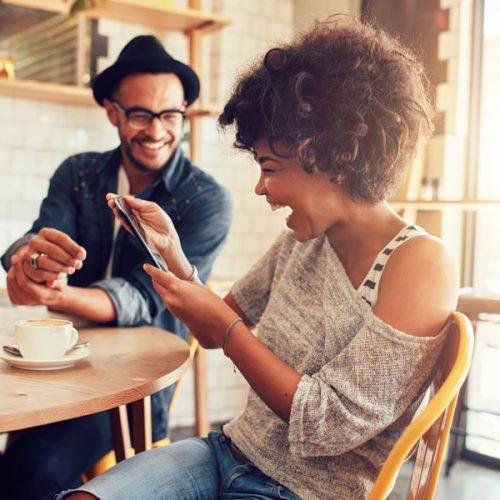 Pareja Boricua compartiendo en un café, mirando un celular y riendo / Puerto Ricans couple laughing at a cafe while watching a cell phone