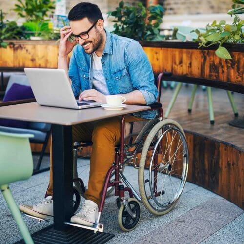 Hombre en sillas de rueda usando laptop